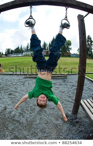 Young Boy Hanging Upside Down By His Feet At A Playground